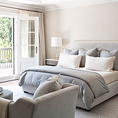 Jennifer Worts Design - bedrooms - gray duvet, gray shams, gray bedding, light gray headboard, light gray velvet headboard, king bed, king bed ideas, geometric rug, white and gray geometric rug, french doors, gray french doors, bedroom sitting area, two tone nightstands,