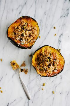 Quinoa Stuffed Acorn Squash 2 acorn squash, halved and seeds removed* 2 tbsp. olive oil Coarse sea salt and pepper 1 c. quinoa, rinsed 2 c. vegetable broth or water 1/4 c. minced red onion 2 tbsp. fresh parsley, minced 1/2 c. raisins 1/4 c. toasted pecans 2 tbsp. balsamic vinegar 2 tbsp. olive oil 1/4 c. feta or parmesan cheese (optional) toasted pepitas for garnish