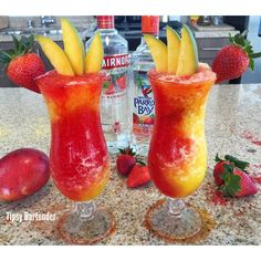 MANGOS IN PARADISE Orange Layer: 1 1/2 oz Mango Rum/ 2 1/2 oz Mango Daiquiri Mix/ Ice Strawberry Layer: 1 1/2 oz Strawberry Rum/ 2 1/2 oz Strawberry Daiquiri Mix/ Ice Garnish: Mango Slices/ Strawberry/ Rim with colored sugar