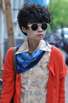 Perfectly put: fluffy, cropped hair; large, beige-rimmed shades; colourful neckerchief and cardigan.