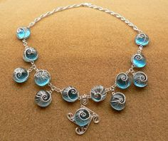 Blue Woven Snail necklace by Ioana Sava made with  blue glass and silver plated wire