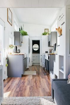 The kitchen features lovely grey cabinets, butcher block counters, a farmhouse sink, a four burner gas range, and an apartment size refrigerator.