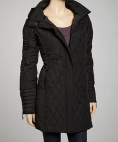 Stay wonderfully warm in this classic quilted coat. The dual zipper and button closure creates a toasty interior environment, while exterior pockets ensure hands stay cozy too. The handy hood zips off for fair-weather wear.