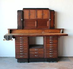 This is an amazing antique wooden watchmakers/jewelers desk workbench. The patina of the wood, the deco style and metal handles of this piece are priceless. The cabinet is in solid condition featuring 21 drawers of varying sizes, some with brackets that once held tools in place (easily removable). The hutch portion contains several storage areas concealed behind sliding doors and cabinets. THE UNIT IS 2 PIECES, so the hutch can be removed and just the cabinet portion can be used as a des...