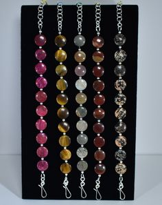 Non-stretch gemstone bracelet series from Cohee Jewelry: From left to right... Pink Crazy Lace Agate, $84.95. Tiger Eye, $84.95. Polychrome Jasper, $77.50. Apple Jasper, $82.50. Mexican Red Snowflake Jasper, $84.95. These are all 12 mm coin shaped gemstones. 7 1/2 inches plus 1 inch soldered ring extension. Hook type clasp and extension are handmade from sterling silver.  Visit my website to see more.