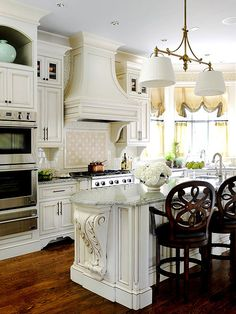 The homeowners' love of French city style, such as big moldings and formal details, inspired this kitchen's colors and textures. Cabinets dressed in decorative details with a rich, glazed finish give this corner kitchen a welcoming French feel. Dark wood floors and barstools balance the lighter tones of the cabinetry./