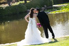 Bride and Groom kiss by the pond  www.proimageweddings.com  www.cateringconnect.com