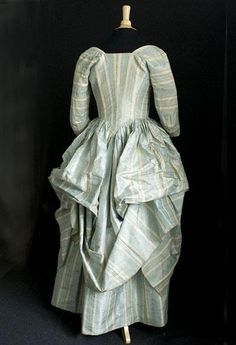 Rear view, robe à la polonaise, 1770s-1780s. Silk damask with scalloped stripes of heavenly robin's egg blue and ivory. The blue stripes have alternating patterns of small diamonds and window-pane plaid.