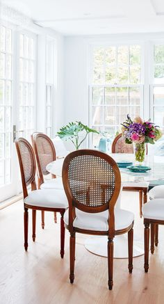 Defined by a mix of old and new, the dining area features a Mid-Century Modern Saarinen dining table surrounded by Louis XVI-style dining chairs with wipeable white vinyl seats. Antique Dining Tables, Black Dining Chairs, Teak Dining Table, Old Chairs, Dining Room Chairs, Modern Chairs, Dining Area, White Chairs, Office Chairs