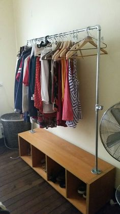 Industrial DIY clothes rack made with galvanized steel piping and an old reclaimed shelf for storage underneath.