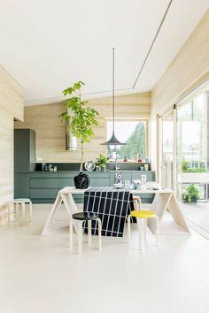 Des éléments de cuisine vert foncé pour mettre en valeur une cuisine en bois clair