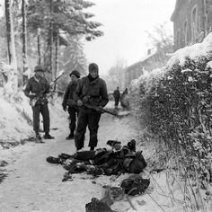 Allied troops and dead German soldier in the snow.
