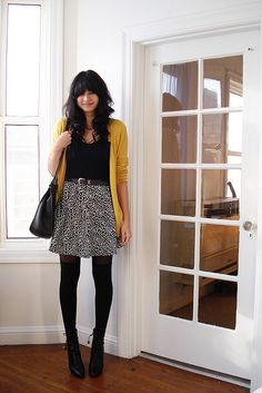 Mustard cardigan, black top, black/white skirt, black tights, & black shoes.