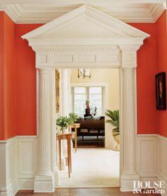 Orange lacquered walls highlight a doorway's classic pediment. #houseandgarden