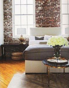 25 gorgeous bedroom decorating ideas - exposed brick wall, chic gold round table at the foot of the bed with a large bouquet of flowers