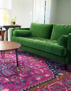 Article Sven Grass Green sofa and bright pink rug in a colorful eclectic living room