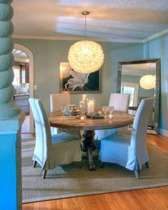 The casual, but elegant, linen slip covered parsons chairs, atop a sea grass rug, coupled with a reclaimed wood dining table, gives this space a relaxed feel. The large floor mirror, round silver tipped shell light fixture, and art gives this room its elegant touch.
