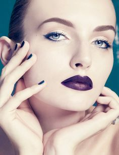 Deep purple lipstick, sapphire blue eyeliner, flawless complexion and dark nails.