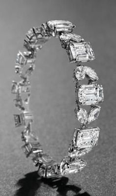 A MAGNIFICENT DIAMOND BRACELET, BY VAN CLEEF & ARPELS   Set with eleven rectangular-cut diamonds, weighing approximately 5.71 to 2.72 carats, interspersed by twin marquise-shaped diamond links, 1966, 17.0 cm, with French assay marks for platinum and gold  Signed Van Cleef & Arpels,