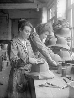 Two women workers cover Army tropical helmets for the firm of Messrs E Day in St Albans. A pile of completed helmets can be seen on the bench beside them. 1918.