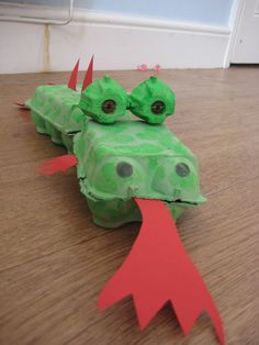 Recycled Egg Box Dragon. You'll need 3 egg boxes, green paint, a paint brush, red paper, 2 treasury tags, glue/sticky tape, red and black felt pens, and scissors.