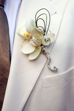 White Phalaenopsis Orchids Are Even More Stunning When Accented With Swirls Of Silver Wire And Strands Of Grass.