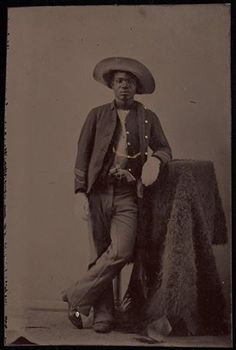 BUFFALO SOLDIER A studio portrait of an unidentified African American soldier posing with buffalo hide. ca. 1860-1880.