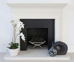 The stark difference between the clean white mantle and the matte black fireplace is an eyecatchers. The orchid placed next to the fireplace really softens it up in a nice way. Marble Hearth, Granite Hearth, Marble Fireplace Surround, Paint Fireplace, Concrete Fireplace, Fireplace Hearth, Marble Fireplaces, Fireplace Surrounds, Fireplace Design