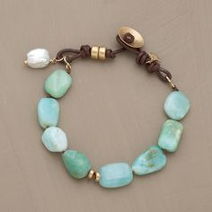 """SANTA FE SKIES BRACELET--Naomi Herndon interprets Santa Fe summer skies: Peruvian opals for the beautiful blues, satin-finished 14kt gold for the sun, a cultured nugget pearl for the rare cloud. Leather loop and gold button clasp. Exclusive. Handmade in USA. Approx. 7-1/2""""L.  $530"""