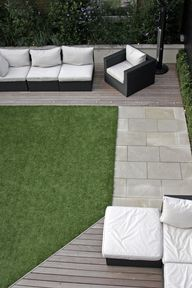 contemporary patio/seating area with pale decking and stone path around an artificial lawn - Outdoor Creations -