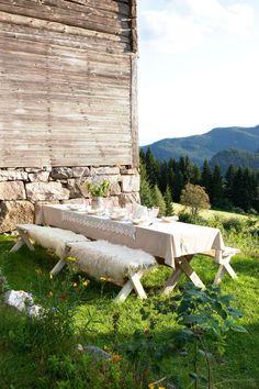 GOD PLASS: Det er plass til mange på langbenkene rundt bordet. Myke skinn er behagelig å sitte på selv i sommervarmen.