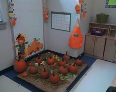 Our pumpkin patch. In the fall, I love creating the pumpkin patch in our dramatic play. This is last years picture.  Dollar store hangers on the wall, pumpkins, gourds, straw, and ripped green paper on top of a cardboard box on the floor.