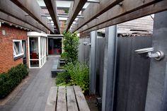 Design pergola in smalle strakke tuin. Niet alleen de pergola is van design kwaliteit, ook bij de schutting en de waterpartij is veel aandacht aan de vormgeving besteed. Een mooi voorbeeld hoe je van de smalle strook naast het huis een prachtige volwaardige tuin kunt maken. Voor meer info kijk op de etalagepagina van Stoss Hoveniers.