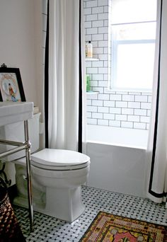 double shower curtain /white with black tape trim/ mosaic marble floor / tribal rug in bathroom  by design manifest