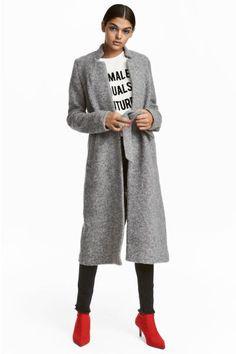 Een jas van gevilte wolmix met een opstaande kraag, een strikceintuur in de taille, steekzakken en een split achter. Zonder sluiting. Ongevoerd.