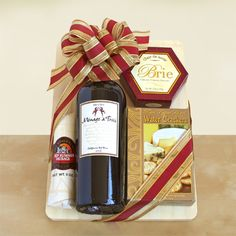 Toast to California Wine  Ready to be enjoyed by friends, family or colleagues, this gift of wine and snacks will delight them all. Toast the good life with a hearty bottle of California red wine stylishly presented atop a handsome wooden cutting board. This delicious gift also includes Brie cheese, water crackers and salami. (Http://deeviele.labellabaskets.com)