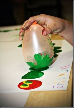 Very Hungry Caterpillar...Balloon painting. I wonder if I could keep the balloons out of the kids mouths long enough to paint with them..