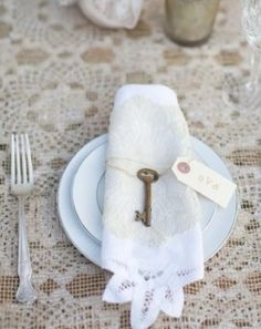 Add vintage key to lace trim napkin table top decor place settings at Wedding reception or shower.  For ideas and goods shop at Estate ReSale & ReDesign, Bonita Springs, FL