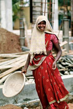A woman worker poses smiling at the building works of the RDT General Hospital extension, in Kalyandurg, Anantapur.