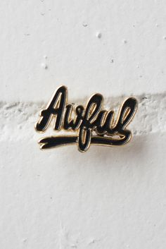 "Soft enamel lapel pin in black and gold featuring our classic ""Awful"" design. Small and subtle at 1"" wide - just the way we like it. Comes on card backing."