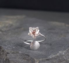 This silver Lotus Blossom and lily pad ring is completely handmade! The Lotus is made of 3 layers of silver with a bronze bead center.