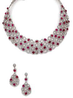 DEMI-PARURE <br>en or gris, comprenant un collier collerette, en ruban souple, agrémenté de cabochons de rubis et de diamants taillés en rose, dans un entourage de petits diamants ronds. <br>Une paire de pendants d'oreilles assortis.  <br>Poids total des rubis : 42 cts environ. <br>Poids total des diamants : 27 cts environ.  <br>Longueur du collier : 36 cm environ. <br>Longueur des pendants : 5 cm environ. <br>Poids brut : 134,5 g.  <br>A ruby, diamond and 18K gold demi-parure comprising a…