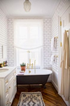 Herringbone floors in bathroom, subway tile, black and white, brass fixtures, and rug.