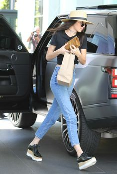 Kendall worked her Stella McCartney shoes with a pair of high-waisted Topshop jeans, a black crop top, a th...