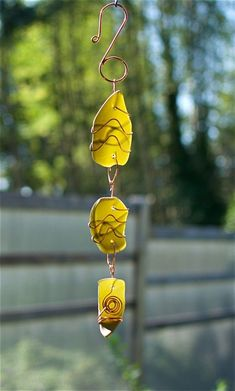A beautiful glass and copper sun catcher- inspired by nature. The 3 copper wrapped artist-made beach glass pieces are smooth with a mat finish. This sun catcher chime measures 15 inches long, from the