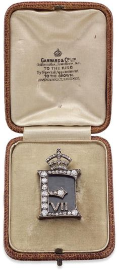 Of Royal Interest: A diamond memorial brooch for H.R.H. Edward VII, circa 1910 The rectangular plaque set with old round brilliant and rose-cut diamonds in the form of an 'E' and 'VII', with a rose-cut diamond-set crown surmount, black silk ground, glazed locket compartment to the reverse, length 34mm, the diamonds estimated to weigh approximately 1.00ct in total, to original fitted case retailed by Garrard & Co., London.