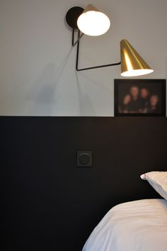 tête de lit chic à l'esprit parisien avec un fond en tablette noir et interrupteur noir. les appliques en cône en or apportent de la lumière par de jolis reflets métalliques.