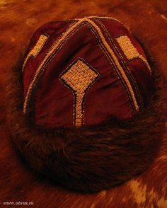 Possament embellishment on a hat - great way of adding in the large square style that's been found in graves - I like it!