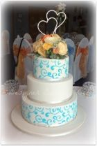 3 tier white wedding cake stencilled with blue royal icing.