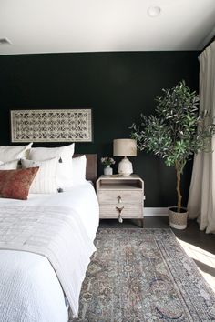 Light wood nightstands in guest bedroom. Obsessed with this dark guest room. You've gotta come see the before and after of this space. From the dark green paint color to the oriental rug to the boho style…it's absolute perfection! Bedroom Green, Green Rooms, Home Bedroom, Dark Master Bedroom, Dark Bedroom Walls, Small Room Bedroom, Green Bedroom Curtains, Mid Century Modern Master Bedroom, Dark Bedrooms
